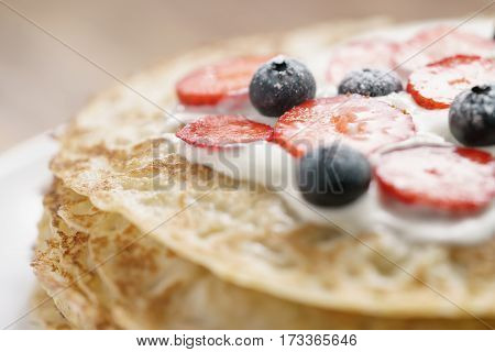 fresh blinis or crepes with fresh berries and cream, sweet food