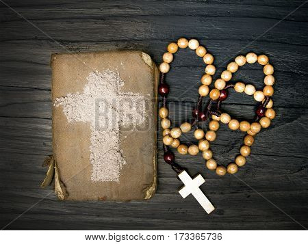 Old Bible rosary and Cross of ash - symbols of Ash Wednesday.