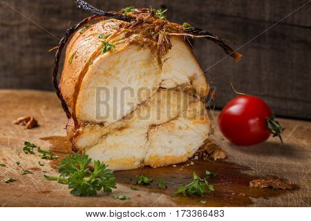 Close up of homemade chicken pastrami with herbs on wooden background