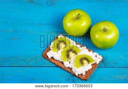 Two green apple and healthy grain sandwich with cream cheese and kiwi slices. A useful homemade breakfast. Vegetarian food. Healthy and tasty food. Copy space.