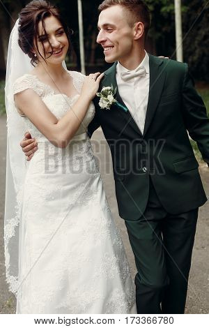 Happy Newlywed Couple Walking Down Summer Park Road, Cheerful Handsome Groom In Stylish Suit Hugging