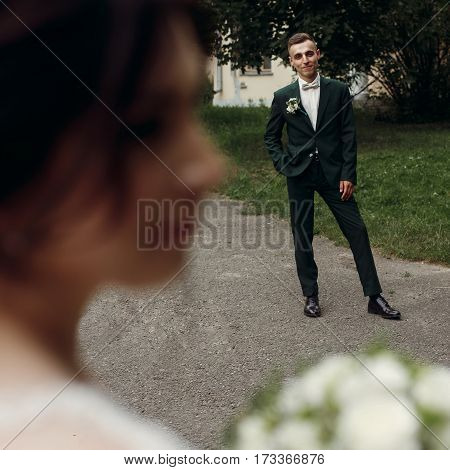 Handsome Happy Groom In Stylish Dark Green Wedding Suit Smiling And Looking At Beautiful Bride In Wh