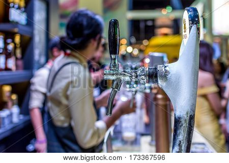 Barman Or Bartender Pouring A Beer From Beer Tap