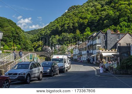 Lynmouth Devon England 13 July 2016: View of the street in the Riverside Road. Parked cars. Walking people. Against the backdrop of hills covered by forests. North Devon Coast