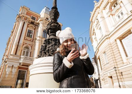 Picture of attractive young lady walking on the street wearing hat while using mobile phone.