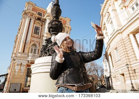 Image of amazing young lady walking on the street wearing hat while make selfie by mobile phone.