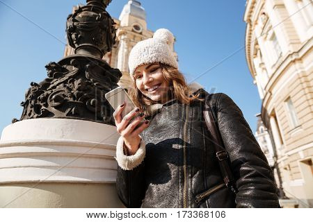 Picture of attractive young woman walking on the street wearing hat while using mobile phone.