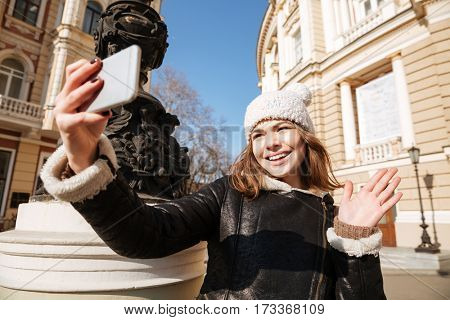 Photo of attractive young lady walking on the street wearing hat while make selfie by mobile phone.