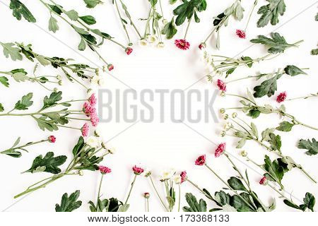 Wreath frame of red and white wildflowers green leaves branches on white background. Flat lay top view. Valentine's background