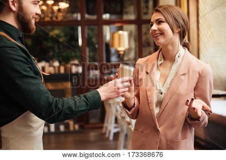 Image of handsome young man waiter standing in cafe gives the coffee to woman client.