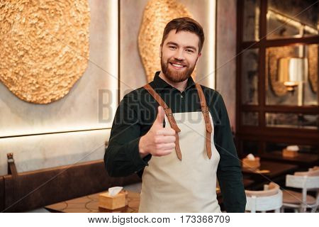 Image of attractive young man waiter standing in cafe with thumbs up gesture. Looking at camera.