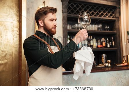Photo of amazing young bearded man bartender standing in cafe. Looking aside and wipe the glass.