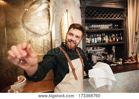 Photo of handsome young bearded man bartender standing in cafe. Looking aside and wipe the glass.