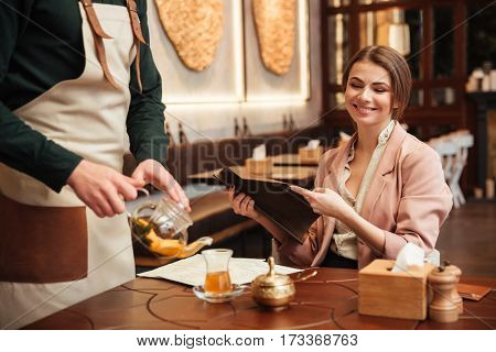 Picture of pretty pretty young woman sitting in cafe. Holding menu list.