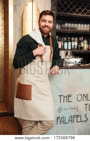 Image of amazing young man bartender standing in cafe. Looking at camera.