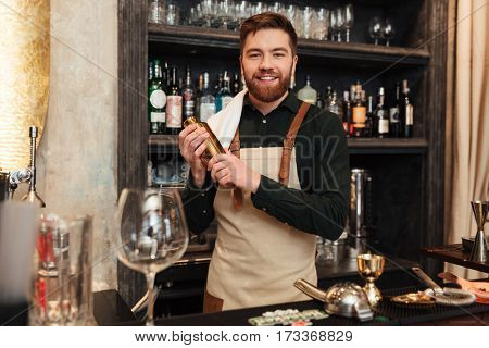 Image of happy young bearded man bartender standing in cafe. Looking at camera holding shaker.