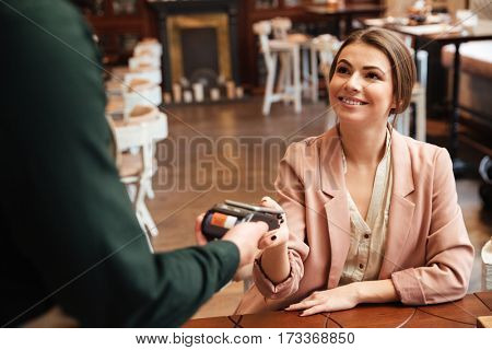 Image of attractive young pretty woman sitting in cafe. Looking at man waiter while pays the order with credit card.