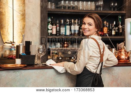Image of pretty young woman bartender standing in cafe. Looking at camera.