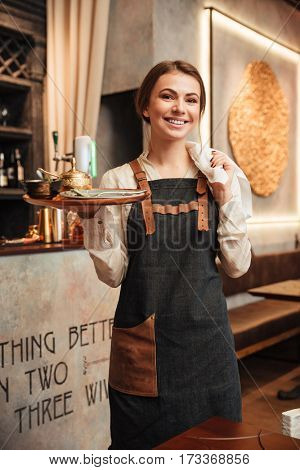 Image of amazing young woman waiter standing in cafe. Looking at camera.