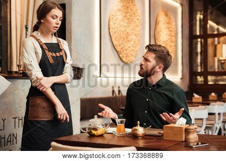Image of angry bearded young man sitting in cafe. Looking at waiter.
