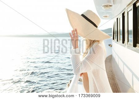 Image of young attractive beautiful woman wearing hat posing on the yacht
