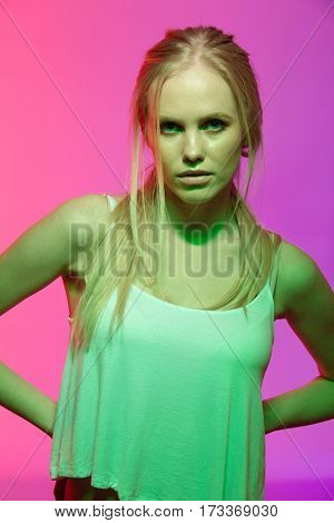 Unusual portrait of serious woman in singlet which holding arms at hip and looking at camera. Vertical image