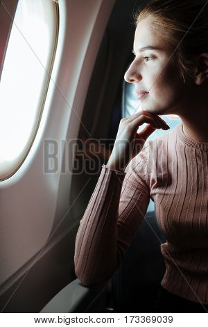 Vertical image of pensive woman which looking in porthole of aircraft