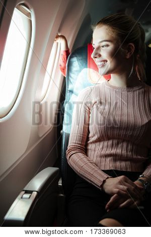 Vertical image of Happy woman which sitting in aircraft and looking at porthole