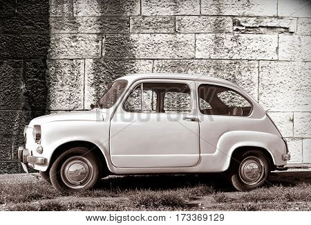 PULA, CROATIA - DECEMBER 9, 2016: Zastava 750 classic white color oldtimer supermini car parked on grass against old wall in Pula Croatia.