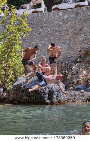Kemer Antalya Turkey - august 26 2014: Vacationers have fun near the mountain river two tourists thrown into the water his friend.