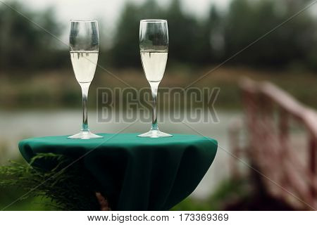 Two Luxury Champagne Glasses At Green Table At Wedding Aisle, Outdoors Near Wooden Bridge And Lake,