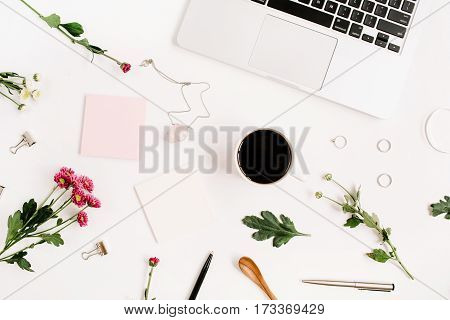 Top view home office table desk pattern. Workspace with laptop wildflowers bouquet coffee cup feminine accessories and office stuff. Flat lay.