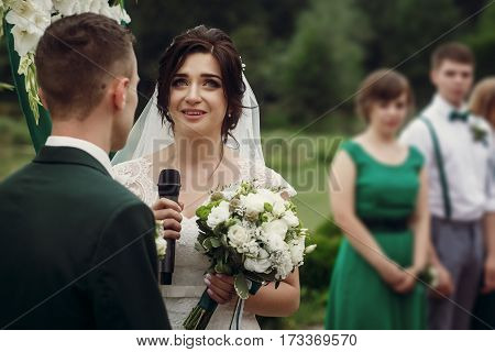 Gorgeous Bride Crying While Taking Vows On Aisle At Lake At Wedding Outdoor Reception And Ceremony.
