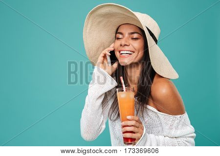 Happy Woman in beachwear which talking on phone with cocktail in hand