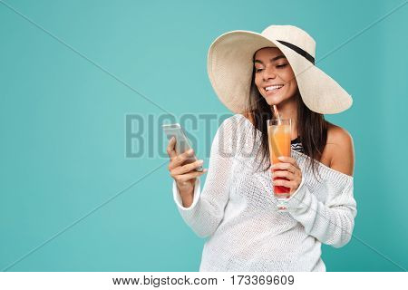 Young Woman in beachwear which using phone and holding cocktail in hand. Isolated turquoise