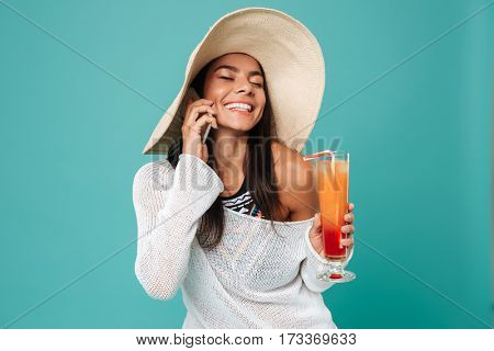 Smiling Woman in beachwear which talking on phone and holding cocktail in hand. Isolated turquoise