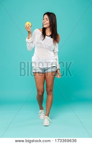 Vertical image of Woman in beachwear with apple in hand. Isolated turquoise background