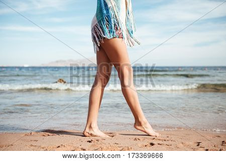 Side view of legs of woman which walking on the beach near the sea. Cropped image