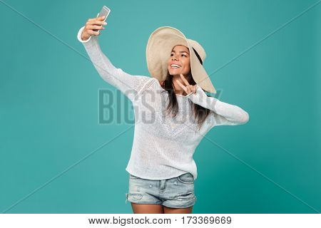 Woman in beachwear which making selfie on phone and showing peace sign at camera. Isolated turquoise background