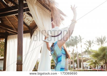 Back view of Brunette woman in beachwear and hat which posing near the alcove and waving away