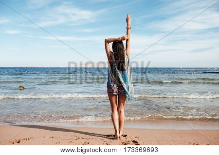 Back view of Young Woman in beachwear which standing on the beach near the sea