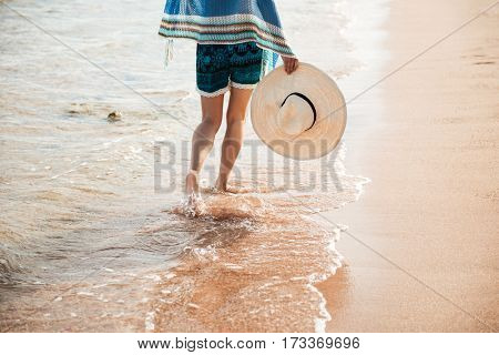 Photo of legs of woman in beachwear which walking on the beach. Back view