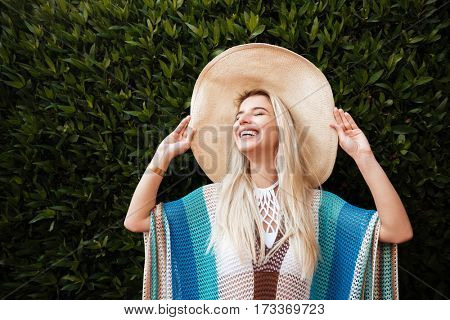 Happy Woman in beachwear and hat standing near the shrub