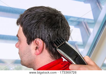Hairdresser Cutting Hair With Electric Hair Clipper In Barber Sh
