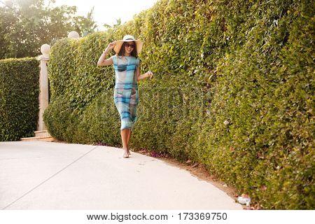 Full length image of Brunette Woman in beachwear which posing near the bush