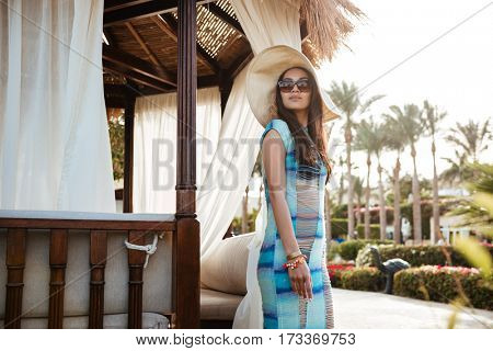 Side view of Brunette woman in beachwear and sunglasses which posing near the alcove and looking away