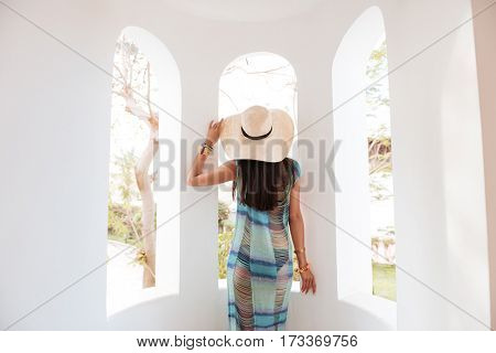 Back view of woman in beachwear which standing on balcony