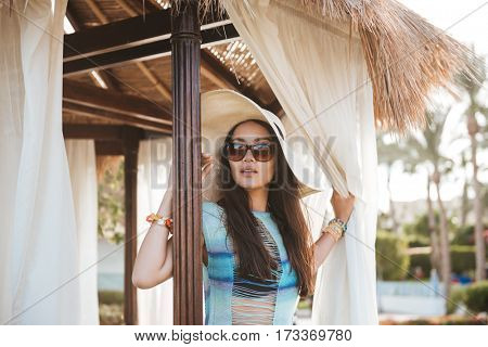 Brunette woman in beachwear and sunglasses which posing in alcove and looking away