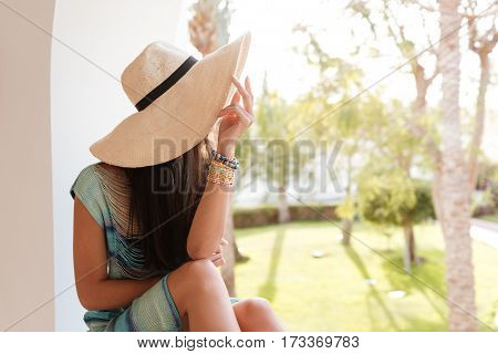 Woman in beachwear which sitting on the edge of balcony and looking away