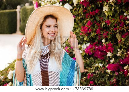 Blonde Woman in beachwear and hat which posing near the flower bush